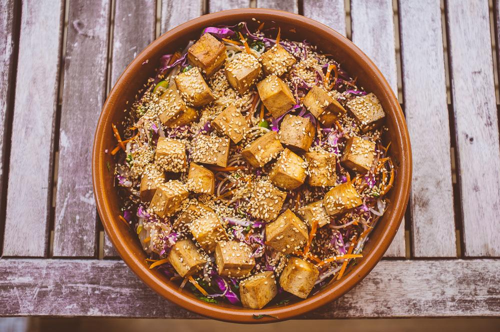 Apelsinmarinerad tofu med nudlar, strimlade grönsaker och rostade sesamfrön.