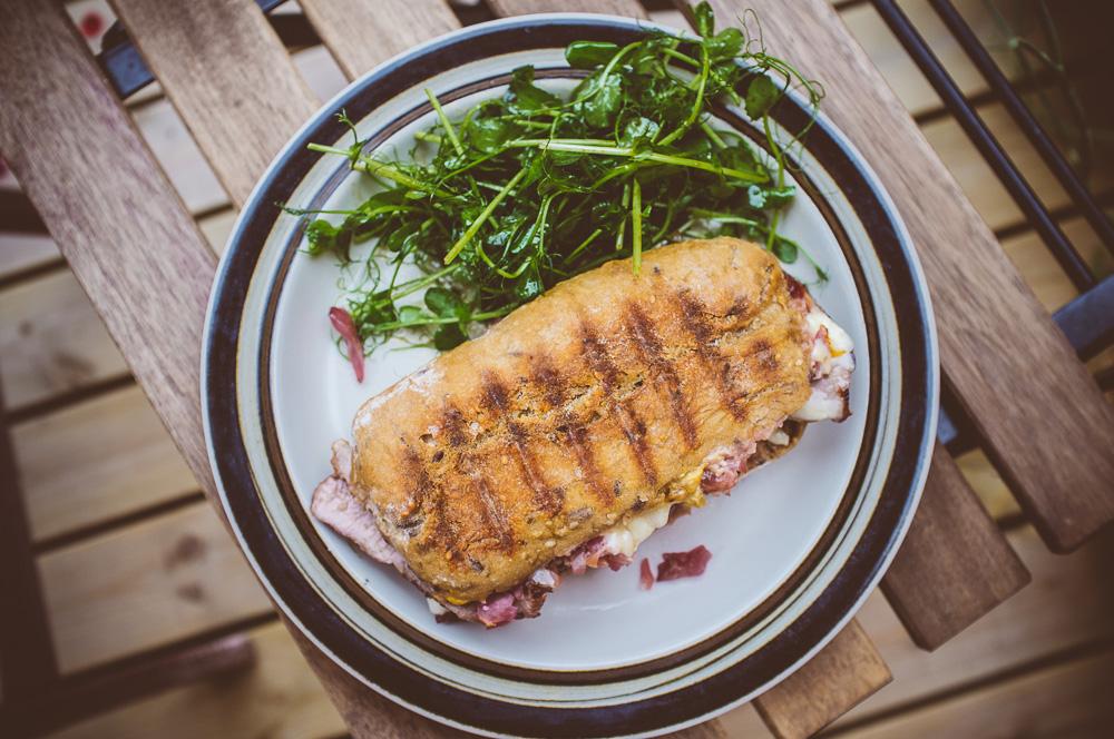 Panini med vildsvinsytterfilé med surrödkål, dijonsenap, ärtskott, cheddarost och plommonsås.