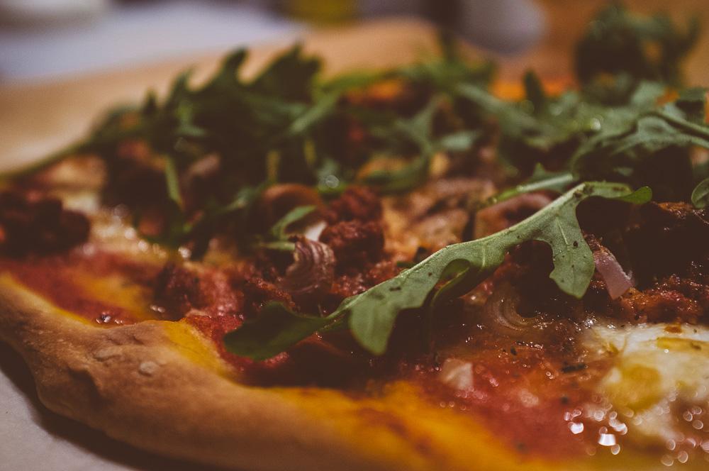 Pizza med färsk salsiccia, schalottenlök, mozzarella, tomatsås och rucola.