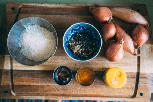 Kokosflingor, hela kryddor, lök, gurkmeja och asafoetida. Ingredienser till kryddpastan.